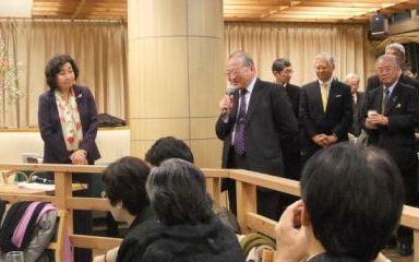 写真・図版 : 出版記念会で挨拶する北野大・明治大学教授。左の女性が崎田裕子さん。後ろに近藤駿介原子力委員会委員長の姿も見える=提供写真
