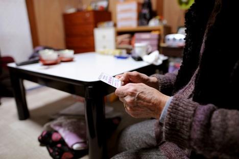 写真・図版 : 緊急連絡カードを常に持ち歩く高齢者。名古屋市内で。