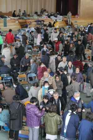 写真・図版 : 避難所の炊き出しに並ぶ人たち。輪になって会話する姿も。その整然とした様子も「世界の模範」か=3月14日、岩手県陸前高田市で西畑志朗撮影