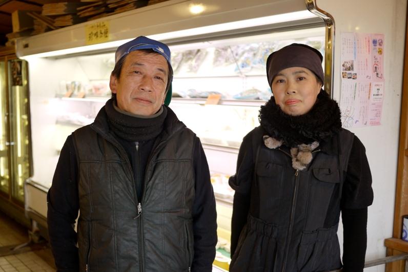 写真・図版 : 震災直後から井戸水を開放するなど、支援活動の最前線に立ってきた海産物店「さんけい」の松田義勝社長(左)と女将の順子さん。=3月21日(写真:小松浩二)