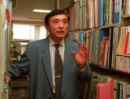 写真・図版 : 原子力資料情報室で書棚を前にした高木仁三郎さん=1997年、東京都内で渡辺剛士撮影
