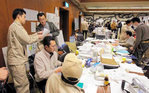 写真・図版 : 「2号機から衝撃音」の報道を聞き、対応に追われる福島県災害対策本部原子力班の職員たち=2011年3月15日午前8時14分、福島市