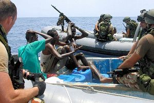 写真・図版 : 小型ボートを浜に引き上げる海賊たち=2009年、ソマリア北東部エイルで