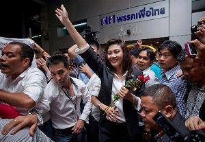 写真・図版 : バンコクで、タイ貢献党本部前に集まった支持者に手を振るインラック氏=7月3日、ロイター