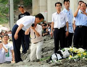 写真・図版 : 200人以上が死傷した脱線事故現場に到着し、献花する温家宝首相(中央)=7月28日、浙江省温州で