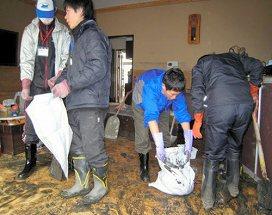 写真・図版 : 宮城・気仙沼で、津波が運んできた大量の泥を取り除くボランティアの学生たち=2011年4月