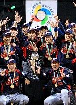 写真・図版 : WBCの優勝トロフィーを囲み笑顔のイチロー(後列中央左)など日本代表=2009年3月23日