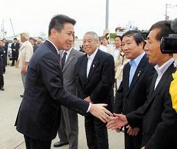 写真・図版 : 択捉へ向かう船に乗り込む前に、見送りの人たちと握手を交わす前原誠司・前外相=8月5日