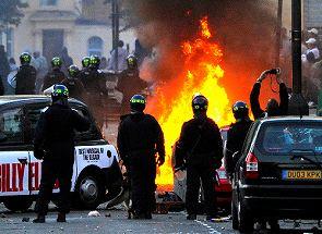 写真・図版 : ロンドン東部で8月8日、炎を上げて燃える車のそばに立つ警察官ら=ロイター