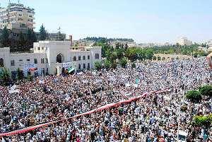 写真・図版 : シリア・ハマ中心部で7月29日、イスラム教の金曜礼拝後にアサド政権打倒を訴えるデモ隊=ロイター