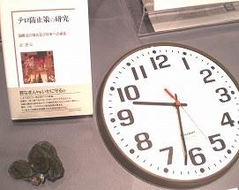写真・図版 : 国立アメリカ歴史博物館の特別展に展示された国防総省の飛行機衝突の際に止まった時計(左は筆者の著書)
