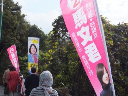 写真・図版 : 公園の道路わきに並んだ選挙候補者の旗