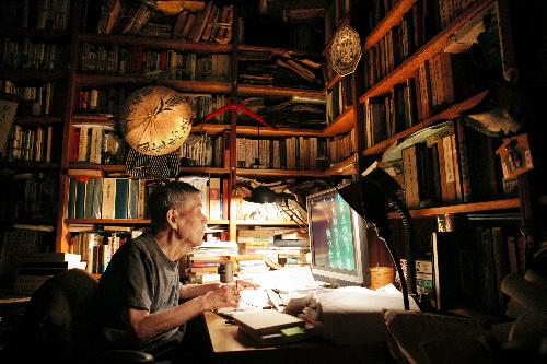 写真・図版 : ルーペで文字を拡大しながら書物を読む吉本隆明さん=2006年7月、東京都・文京区の自宅書斎で