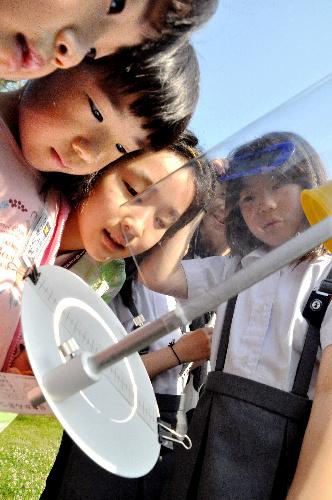 写真・図版 : 5月21日朝、投影板に映った太陽の姿を見る子どもたち=京都府で、籏智広太撮影