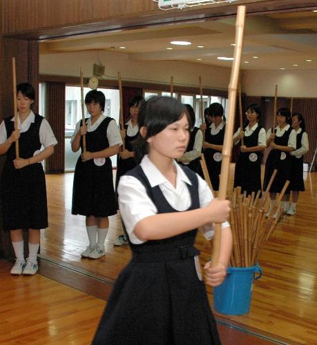 写真・図版 : 竹の棒を持って体育館を行進する=2007年