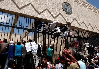 写真・図版 : イエメンの首都サヌアで、反イスラム映像に抗議して米国大使館の門をよじ登る人たち=2012年9月13日、AP