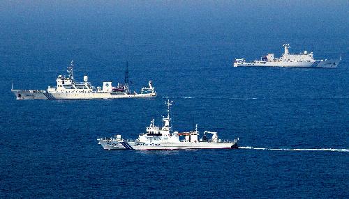 写真・図版 : 尖閣諸島・魚釣島の接続水域で、中国の海洋監視船(奥の2隻)を警戒する海上保安庁の巡視船=2012年9月19日
