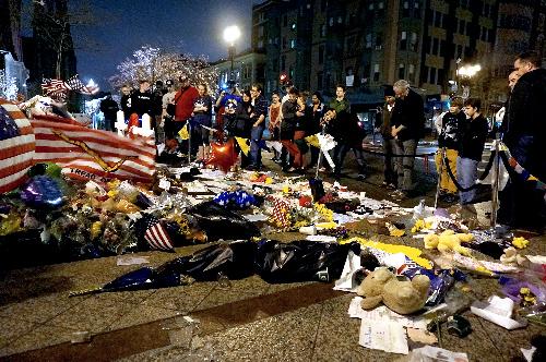 写真・図版 : 爆発があったボストン・マラソンの会場近くに集まり、祈りを捧げる市民たち=2013年4月20日、ボストン