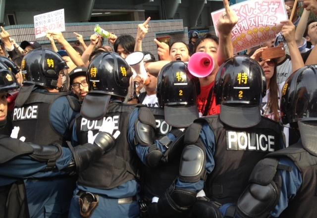 在特会のデモに抗議する人たちと警察官ら=2013年6月30日、東京・新宿区