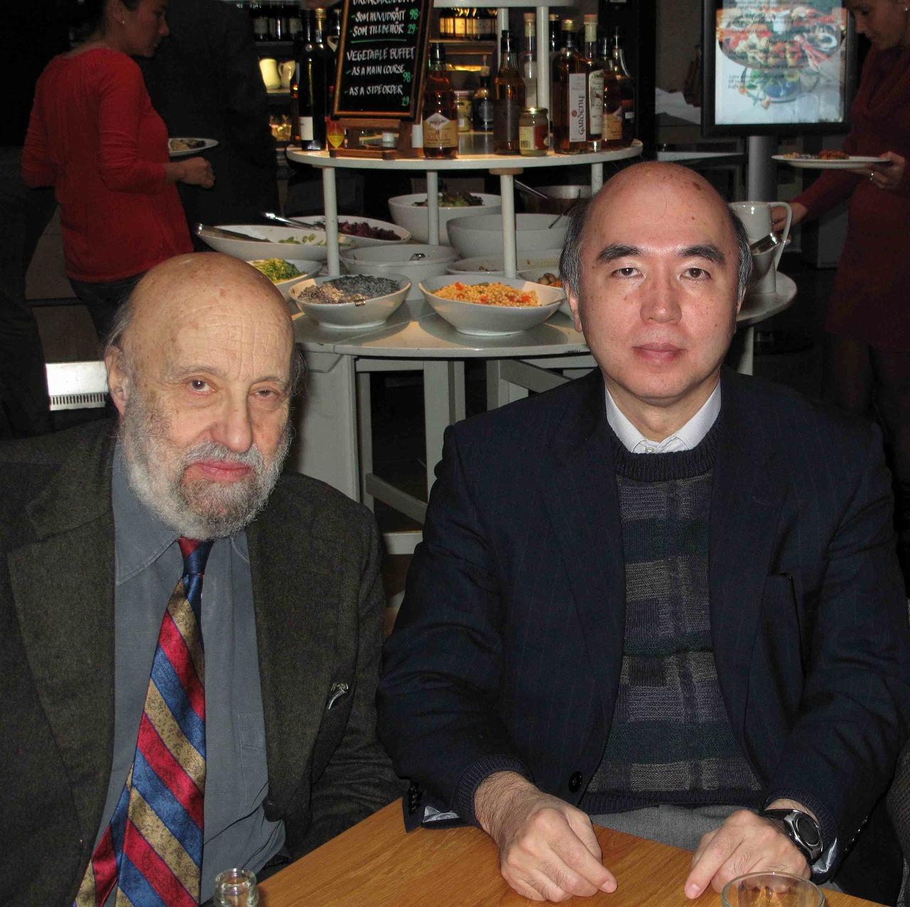 写真・図版 : ノーベル賞講演を前にするジャンニさん(左)と南部さんの弟子の江口徹さん。