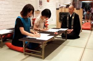 日本では最近、仏教が若い女性の関心を集めている。2012年の丸ビル「高野山カフェ」で写経を体験する女性たち=主催者提供
