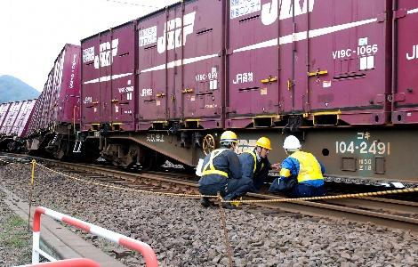 脱線した列車を調べる運輸安全委員会の調査官ら=20日、北海道七飯町