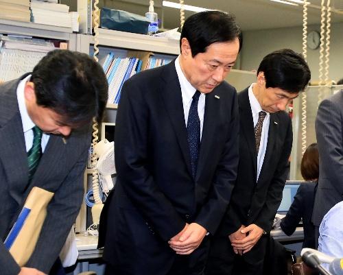 記者会見の冒頭、頭を下げるみずほ銀行の佐藤康博頭取(中央)=2013年10月28日午後、東京都中央区