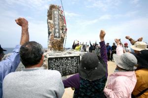 祖国復帰闘争碑を囲んで「主権回復の日」に抗議する人たち=2013年4月23日、沖縄県国頭村の辺戸岬