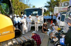 ゲート前に座り込み、沖縄防衛局の重機搬入を阻む住民たち(手前右側)=2011年11月15日、沖縄県東村高江