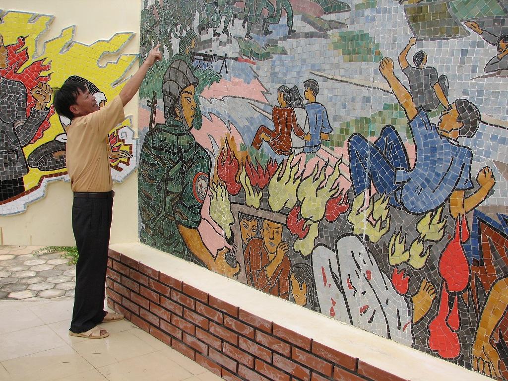ベトナム中部ビンディン省で、韓国軍による 住民虐殺の様子を描いた壁画の前で被害を 語る村人=桜井泉撮影