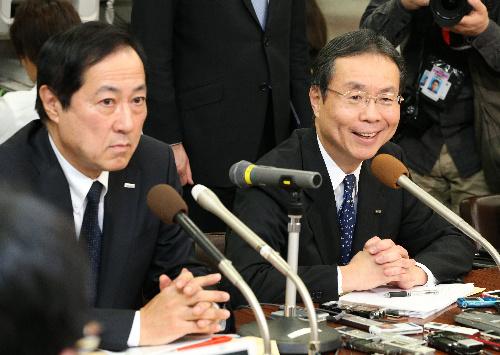 代表権のない取締役に退くことが決まり、会見するみずほ銀行の佐藤康博頭取(左)。右は林信秀次期頭取=2014年1月23日午後5時8分、東京都中央区