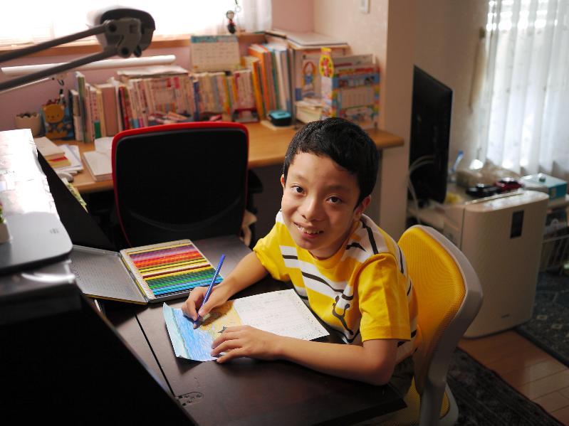 自宅の部屋で。俳句に合わせて絵を描く小林凜くん=20118大阪府岸和田市