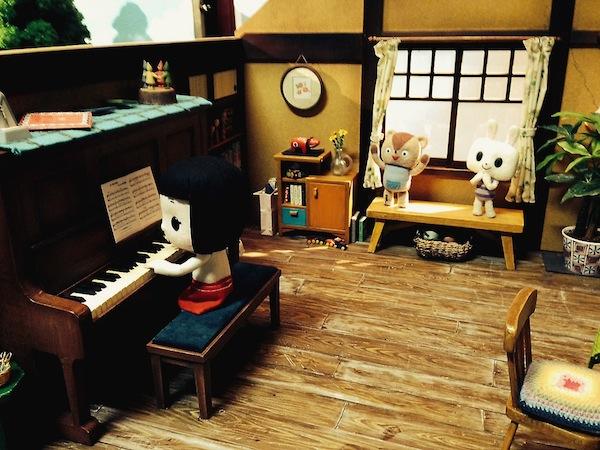 部屋のセット内に配置された人形たちとミニチュア小物。赤べこやこけしなど東北の民芸品も精密に再現