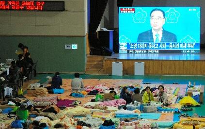 写真・図版 : 沈没した旅客船セウォル号の乗客の家族たちが情報を待つ体育館で、首相辞任のニュースが流れた=2014年4月27日、韓国・珍島