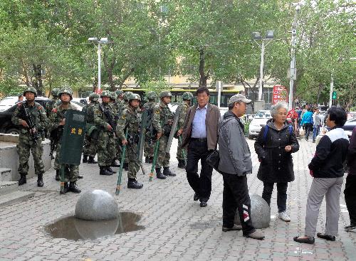 爆発事件から一夜明け、現場付近で周囲を警戒する武装警察官たち=2014年5月23日、ウルムチ