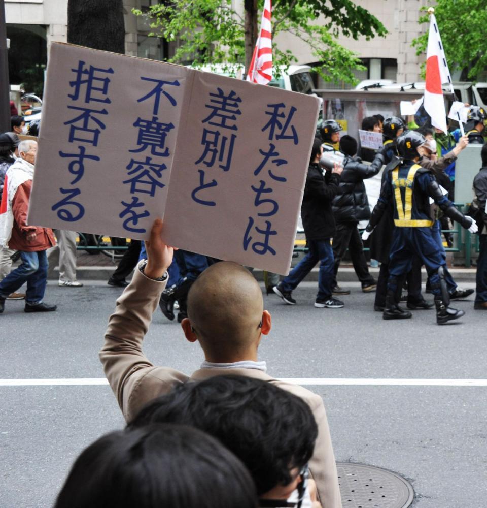 写真・図版 : 外国人排除を訴えるデモ隊(奥)にプラカードを掲げる人たち=2013年4月21日、東京都新宿区