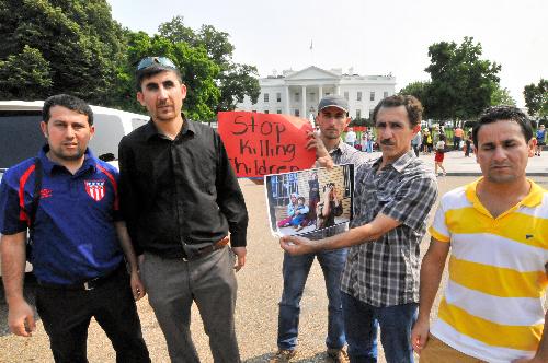 ホワイトハウスの前で米国の早期介入を求める少数宗派ヤジディの信者たち。この8時間後、オバマ大統領が限定空爆を発表=2014年8月7日、ワシントン