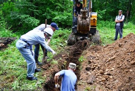 パワーショベルや手彫りで遺骨を探す団員やロシア人作業員たち=2014年7月19日