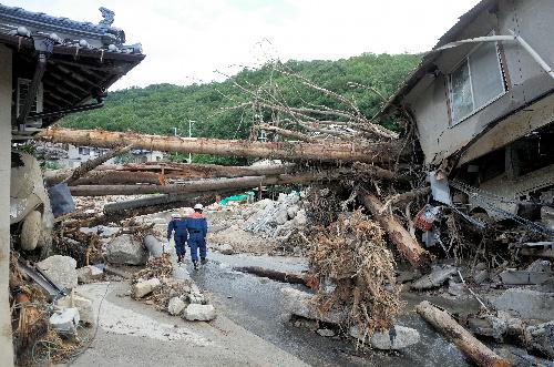 写真・図版 : 広島市安佐南区の現場。流木が住宅に引っかかり、道路を塞いでいた=26日、東山正宜撮影