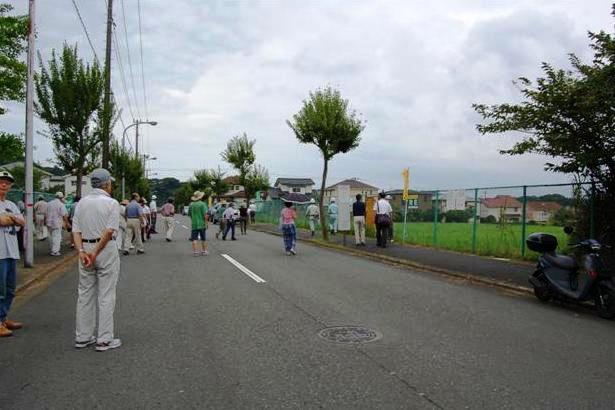 8月25日、「高速横浜環状南線」予定地の地質調査に訪れたNEXCO東日本職員(右奥)を監視する住民たち。沿線住民の根強い反対には背景がある。横浜市は1970年代までに不動産業者に高速道路用地の確保を条件に宅地開発を許可。しかし、不動産業者らは物件説明書に「一般道路予定地」と記載して宅地を販売した。1998年に38名が土地代金の返還を求め市や業者を提訴したが、最高裁で時効を理由に棄却された