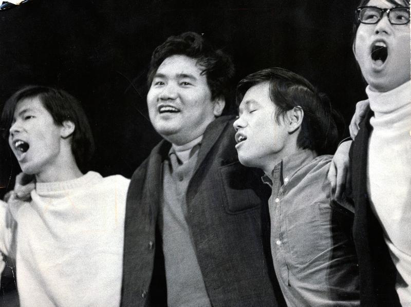 若者たちと肩を組んで反戦ソングを歌う。「週刊アンポ」を発刊する作家(べ平連代表)の小田実(左から二人目)=1969年、東京・板橋区民会館