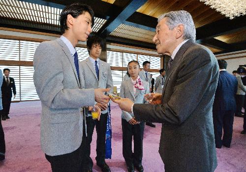 写真・図版 : 羽生結弦選手のオリンピック金メダルを手にする天皇陛下=2014年7月16日、皇居・宮殿(代表撮影)
