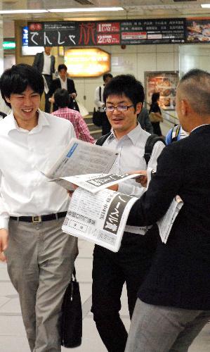写真・図版 : 名鉄名古屋駅では日本人3人のノーベル賞受賞を報じる朝日新聞の号外が配られた=名古屋市