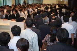 写真・図版 : 福岡市で開かれた九州電力の「再生可能エネルギー買い取り中断」の説明会。午前の説明会が終わり、会場を出る事業者たち(右)。その左側には午後の説明会の開始を待つ行列ができていた。10月1日午後零時28分、福岡市中央区で