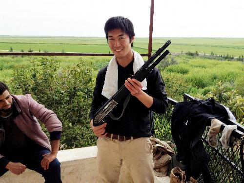 シリアの反政府組織の施設でショットガンを持つ鵜澤佳史さん(右)=2013年4月、鵜澤さん提供