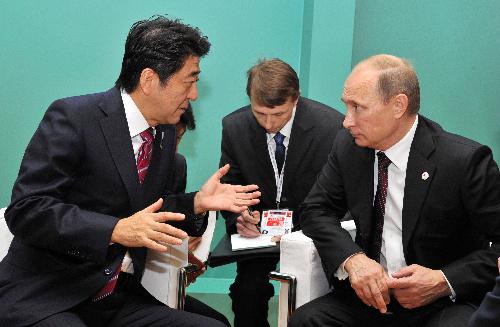 10月17日、イタリアのミラノで会談する安倍晋三首相とプーチン大統領=内閣広報室提供