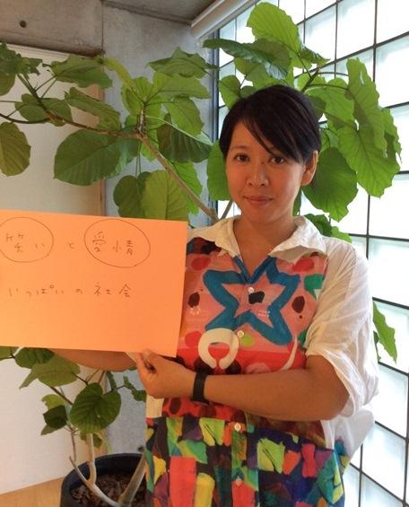 「『笑い』と『愛情』いっぱいの社会」という自身が目指す社会のフリップをもつ佐藤よし子さん。着ている服は、本文中で紹介されているダウン症の方がデザインしたフラボアのもの。