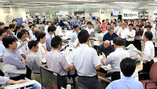報道・編成局のデスク会。吉田調書の記事取り消しについての会見が行われた日は、通常より多くの社員が加わり、意見が交わされた=9月11日午後10時28分、東京本社