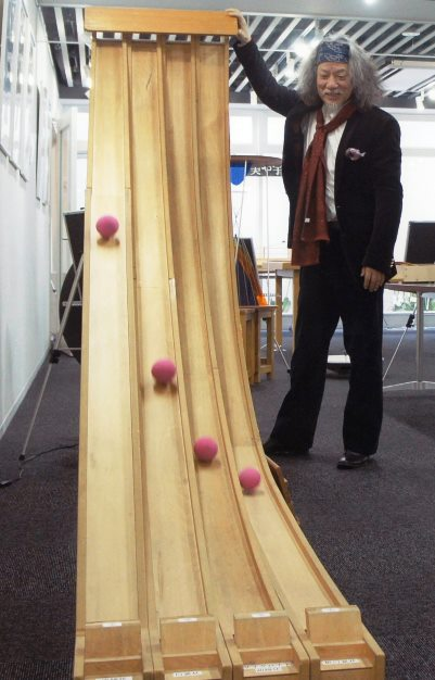 写真・図版 : 東京理科大数学体験館で、曲線の種類とボールが落ちるスピードの関係を知る実験を説明する筆者