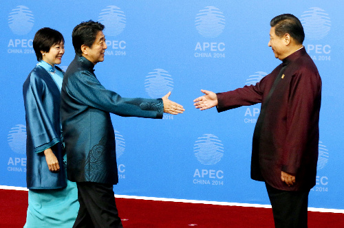 APEC首脳会議が開幕、歓迎夕食会で中国の習近平国家主席(右)に迎えられる安倍晋三首相と昭恵夫人=2014年11月10日、北京の国家水泳センター、代表撮影
